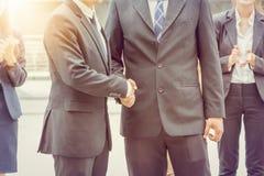 在城市的商人握手在办公室外 免版税库存照片