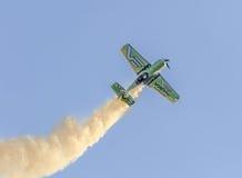 在城市的天空的特技飞机飞行员Jurgis Kairys训练 有踪影烟的, airbandits, aeroshow色的飞机 免版税库存图片