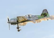 在城市的天空的特技飞机飞行员Jurgis Kairys训练 有踪影烟的, airbandits, aeroshow色的飞机 库存照片