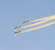 在城市的天空的特技飞机飞行员Jurgis Kairys训练 有踪影烟的, airbandits, aeroshow色的飞机 免版税图库摄影