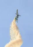 在城市的天空的特技飞机飞行员Jurgis Kairys训练 有踪影烟的, airbandits, aeroshow色的飞机 图库摄影