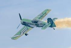 在城市的天空的特技飞机飞行员Jurgis Kairys训练 有踪影烟的, airbandits, aeroshow色的飞机 免版税库存照片