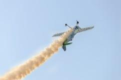 在城市的天空的特技飞机飞行员Jurgis Kairys训练 有踪影烟的, airbandits, aeroshow色的飞机 库存图片