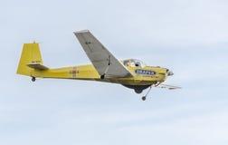 在城市的天空的特技motorplane (sailplane)飞行员训练 ICA IS-28, aeroshow 图库摄影