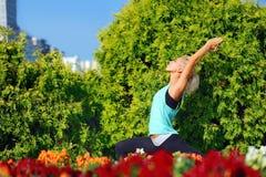 在城市的开花的角落的女子实践的瑜伽 免版税库存图片