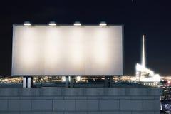 在城市的背景的大空的广告牌在晚上 库存照片