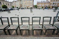 在城市的艺术设施金属化在被修补的街道上的椅子 库存照片