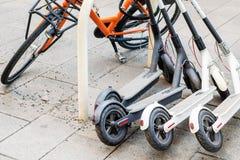 在城市街道上和电滑行车停放的自行车 自助街道运输出租服务 租都市车与 免版税库存照片