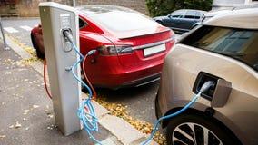 在城市街道上的充电站 缆绳被连接到驻地,充电两辆电车 处理显示闪光 股票录像