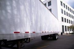 在城市街道上的半拖车有在背景的办公楼的 库存照片