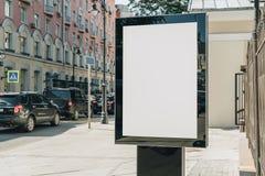 在城市街道上的垂直的空白的发光的广告牌 在背景大厦和路有汽车的 嘲笑 库存照片