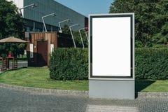在城市街道上的垂直的空白的发光的广告牌 在背景大厦和路有汽车的 嘲笑 免版税库存照片