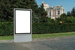 在城市街道上的垂直的空白的发光的广告牌 在背景大厦和路有汽车的 嘲笑 库存图片