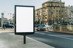在城市街道上的垂直的空白的发光的广告牌 在背景大厦和路有汽车的 嘲笑 图库摄影