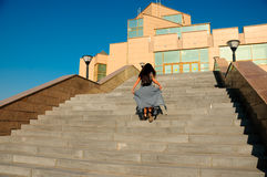 在城市街道上的妇女攀登台阶 免版税图库摄影