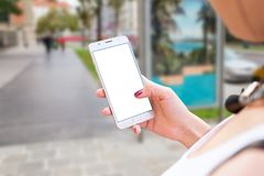 在城市街道上的妇女用途手机 图库摄影
