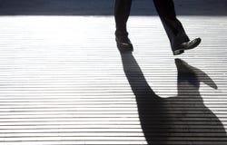 在城市街道上的模糊的一个人` s腿 免版税库存图片