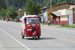 在城市街道上的秘鲁红色tuk-tuk 库存照片