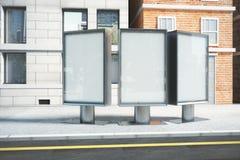 在城市街道上的空白的白色广告牌在日出 库存图片