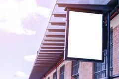 在城市街道上的空白的白色广告牌 在背景街道和大厦 嘲笑 在街道上的海报 文本的空的空间 复制 免版税图库摄影