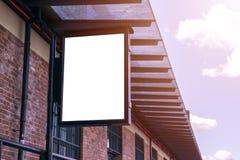 在城市街道上的空白的白色广告牌 在背景街道和岩石 嘲笑 在街道上的海报 文本的空的空间 复制sp 免版税图库摄影