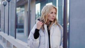 在城市街道上的美丽的妇女 一个年轻金发碧眼的女人的画象下来夹克的 影视素材