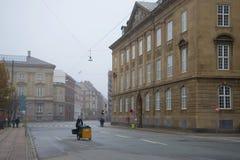 在城市街道上的邮差有雾, 11月早晨 哥本哈根丹麦 库存照片