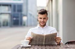 在城市街道咖啡馆的微笑的人读书报纸 库存图片