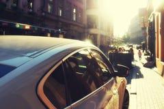 在城市街道在阳光下和孩子上的汽车 图库摄影