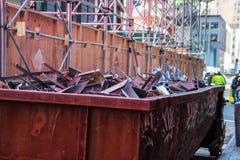 在城市街道工地工作的老生锈的大型垃圾桶 免版税库存图片
