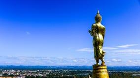 在城市视图的菩萨雕象有天空蔚蓝背景在泰国 免版税库存图片
