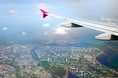 在城市视图翼之下的飞机 免版税库存图片