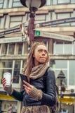 在城市道路标志前面的女性旅游身分 库存图片