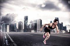 在城市道路的沥青的运动妇女赛跑者 图库摄影