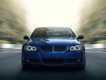 在城市道路的蓝色汽车最快速度驱动 图库摄影