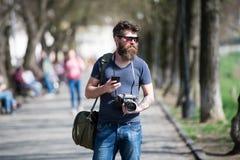 在城市附近的年轻男性摄影师漫步查寻的完善的图片 拿着葡萄酒的时髦的eyewear的有胡子的人 免版税图库摄影