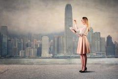 在城市风景前面的端庄的妇女 免版税库存图片