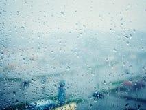 在城市,在湿玻璃窗的水下落下雨 库存图片