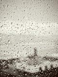 在城市,在湿玻璃窗的水下落,日落下雨 免版税库存图片