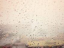 在城市,在湿玻璃窗的水下落,日落下雨 库存图片