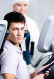 在培训用具的妇女培训在与教练的健身房 库存照片