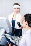 在培训用具的运动妇女培训在与教练的健身房 免版税库存照片