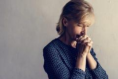 在基督教宗教的白种人妇女祷告信念 免版税库存照片