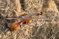 在堆和弓安置的一把小提琴秸杆在领域下 免版税库存照片