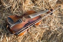 在堆和弓安置的一把小提琴秸杆在领域下 免版税库存图片