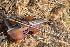在堆和弓安置的一把小提琴秸杆在领域下 免版税图库摄影