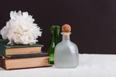 在堆旧书旁边绿化并且结霜了瓶子与牡丹 免版税库存照片