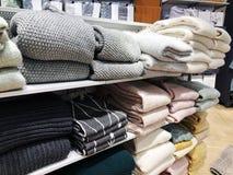 在堆的一条围巾在一张轻的背景正面图的一个白色木架子 库存图片
