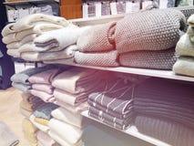 在堆的一条围巾在一张轻的背景正面图的一个白色木架子 库存照片