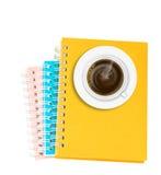 在堆的咖啡在丝毫或笔记本隔绝的圆环包扎工具书 免版税库存图片